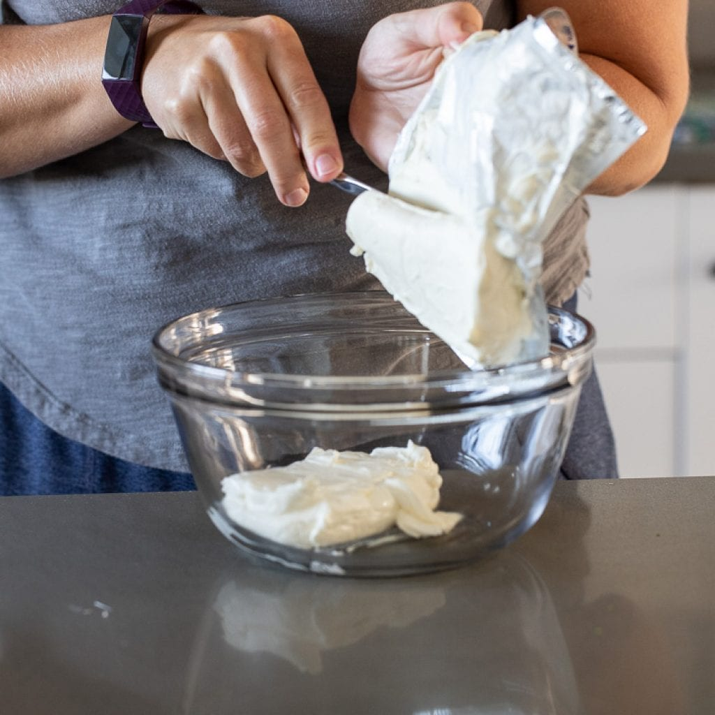 woman adding softened cream cheese to glass bowl