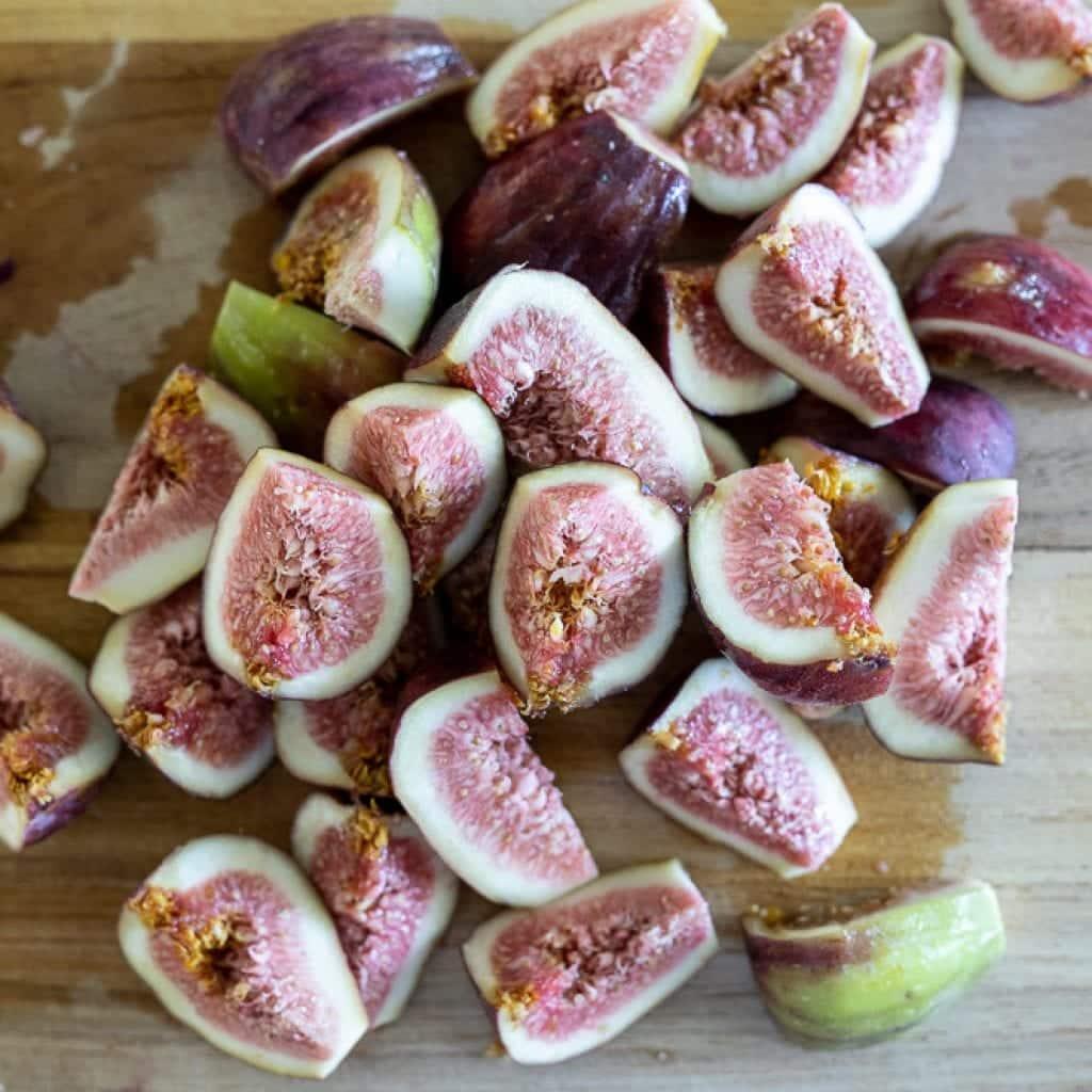 figs quartered on wood cutting board