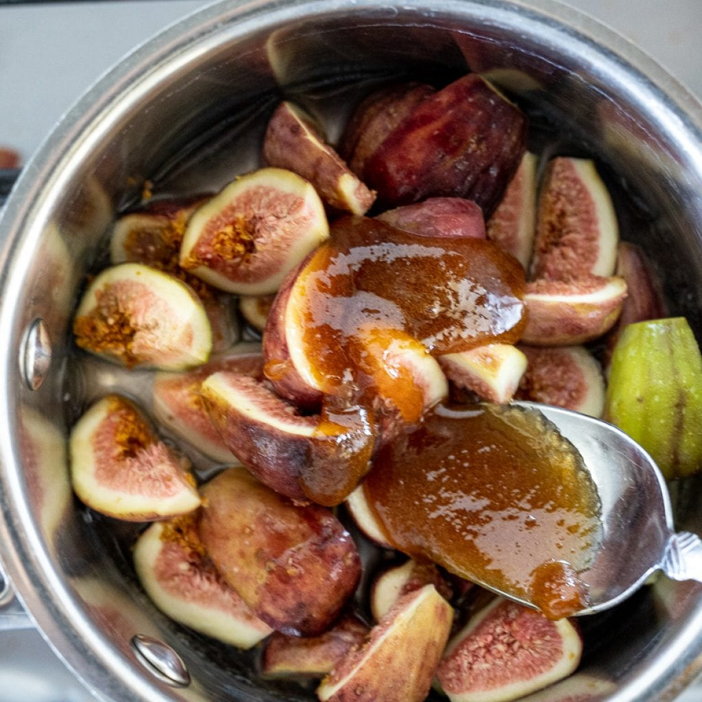 woman adding honey to figs in small pan