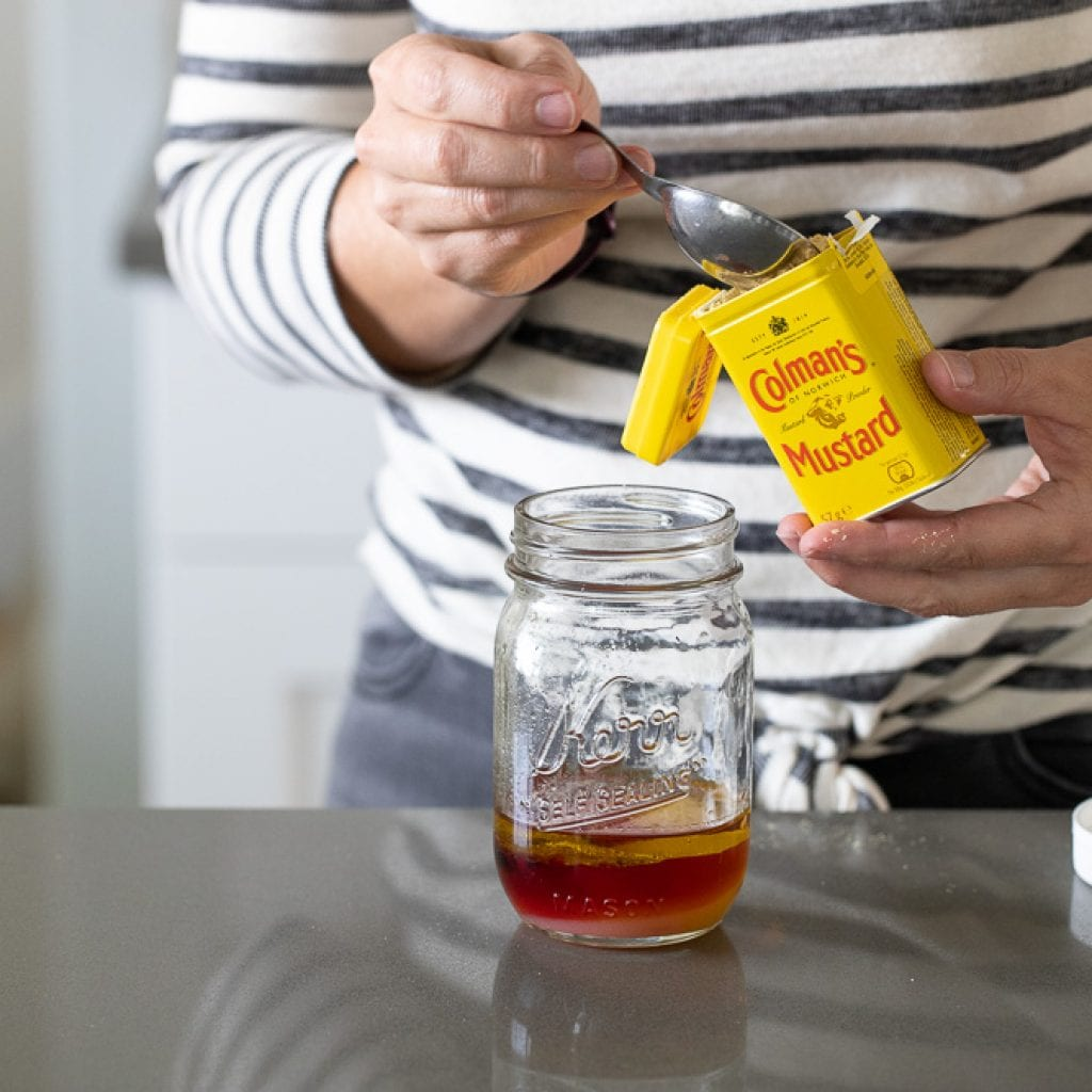 woman adding dry mustard to kerr canning jar for a red wine poppyseed dressing
