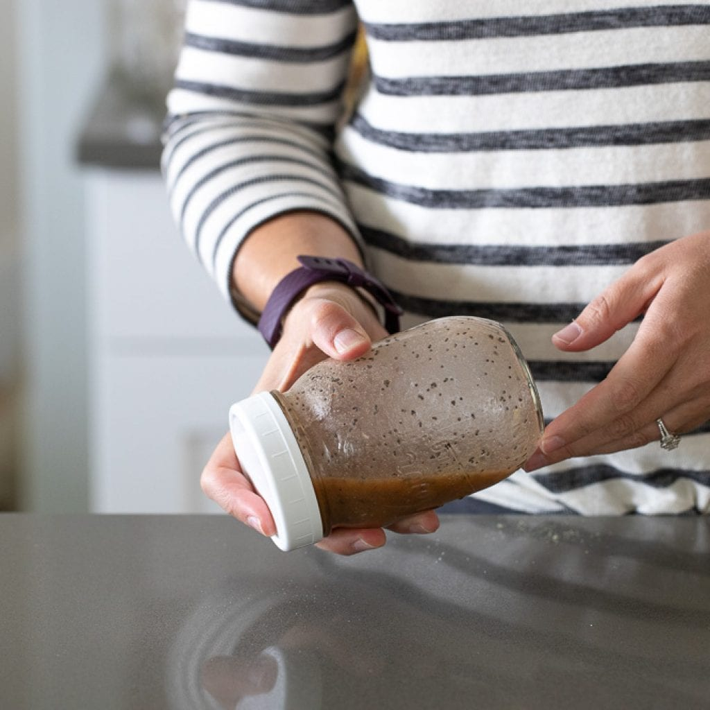 woman shaking red wine poppyseed dressing in kerr canning jar