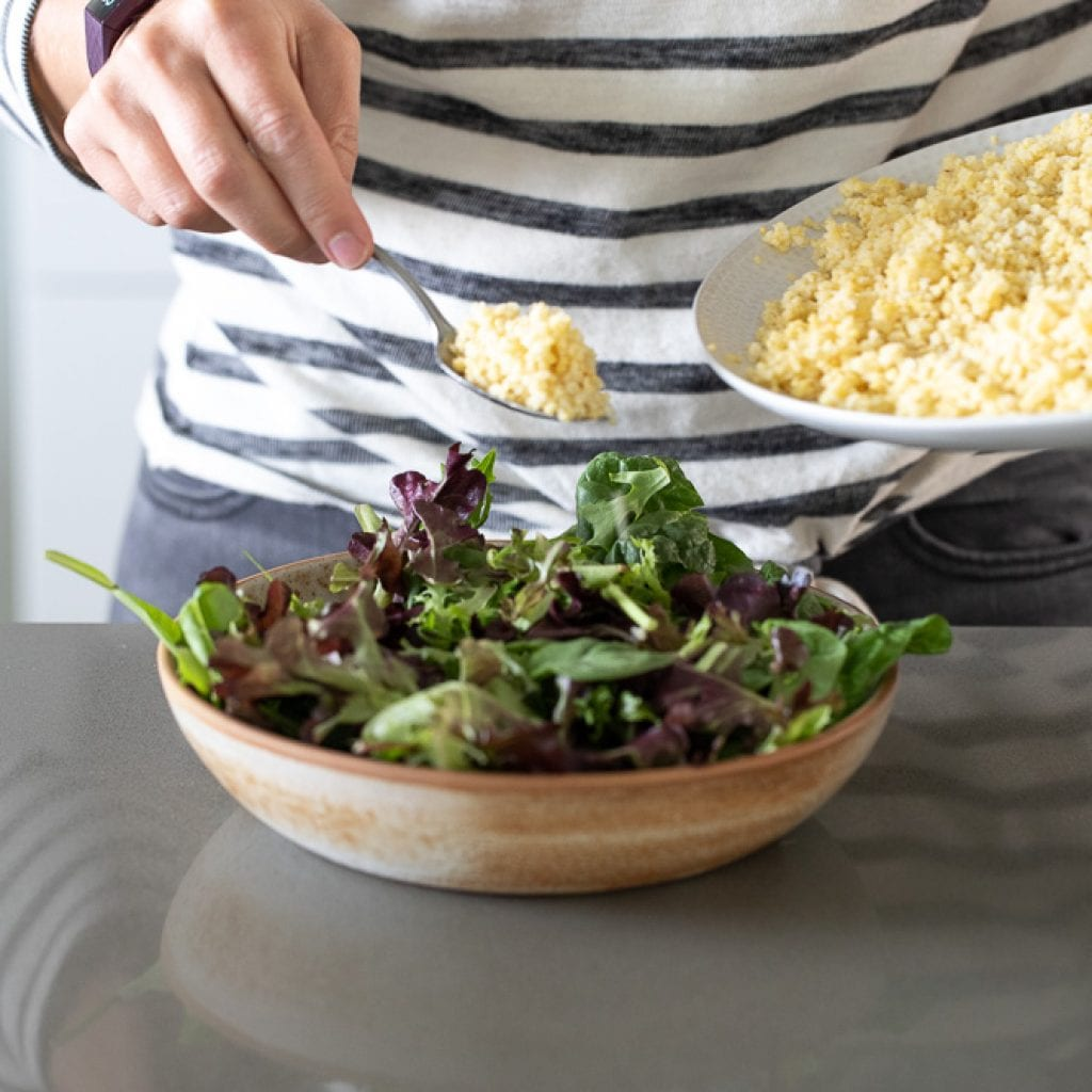woman adding millet to green salad