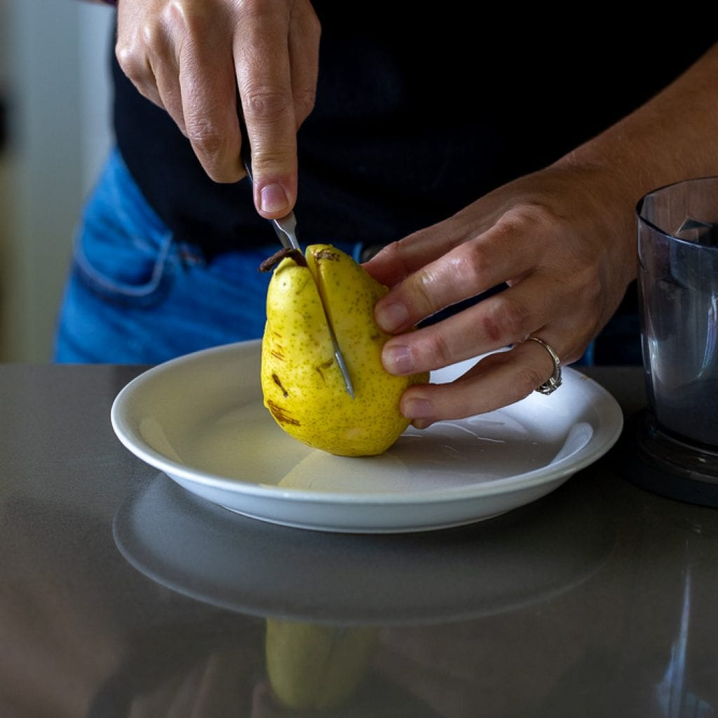 woman cutting a pear in half on small white plate