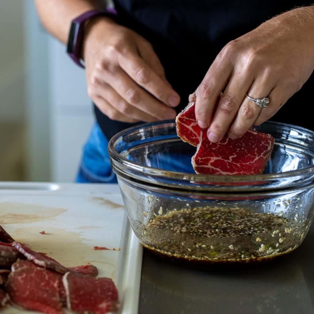 woman adding beef tenderloin slice to a marinade for beef bulgogi