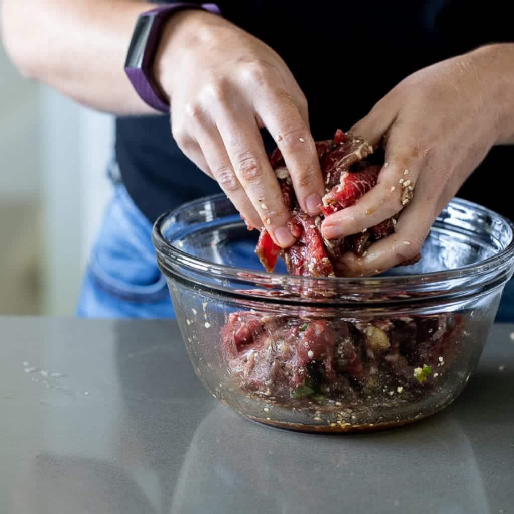 woman mixing beef in marinade for beef bulgogi