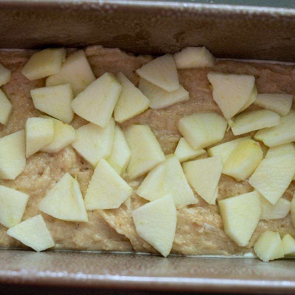 chopped apples on batter in loaf pan for apple loaf