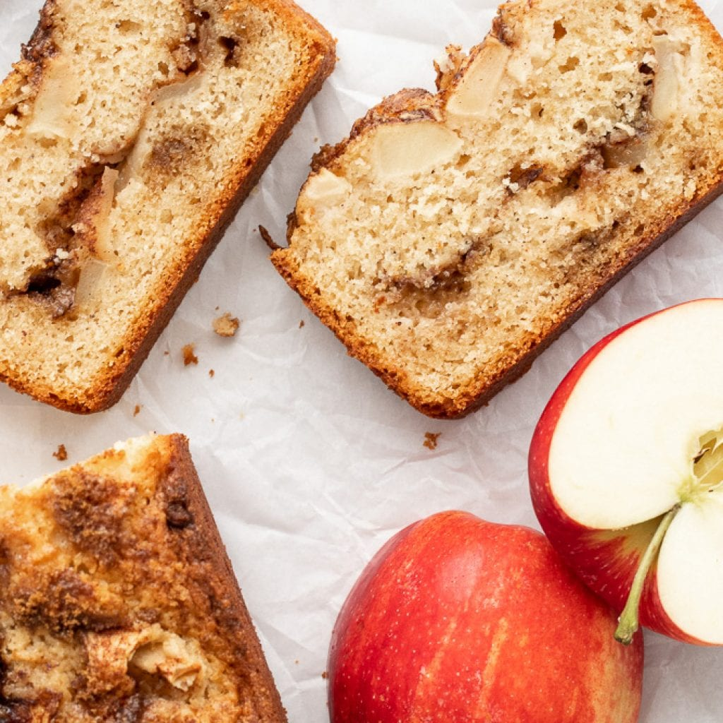 Layered apple and cinnamon loaf sliced with apples on parchment