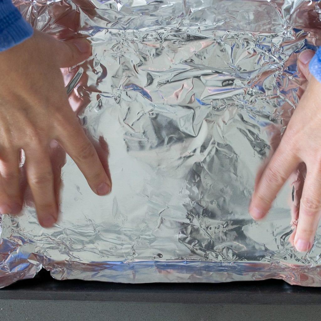 woman pressing aluminum foil into 9x13 pan