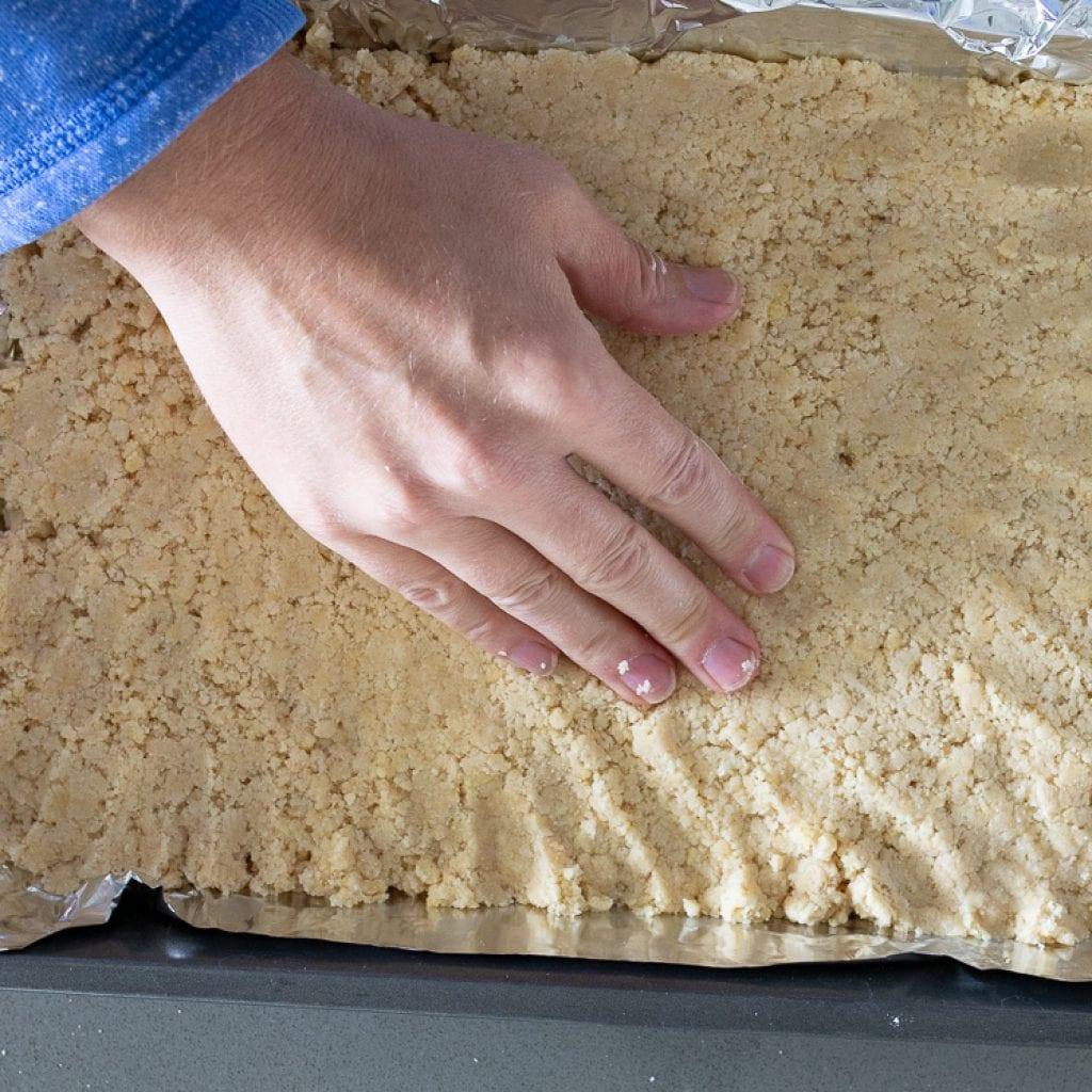 woman pressing shortbread into 9x13 pan for caramel pecan bars