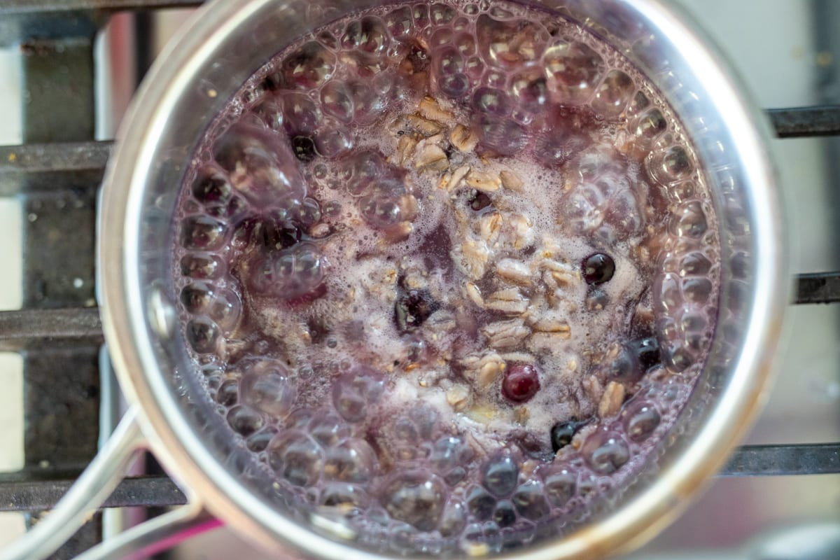 oatmeal cooking in a small stainless steel pan with blueberries