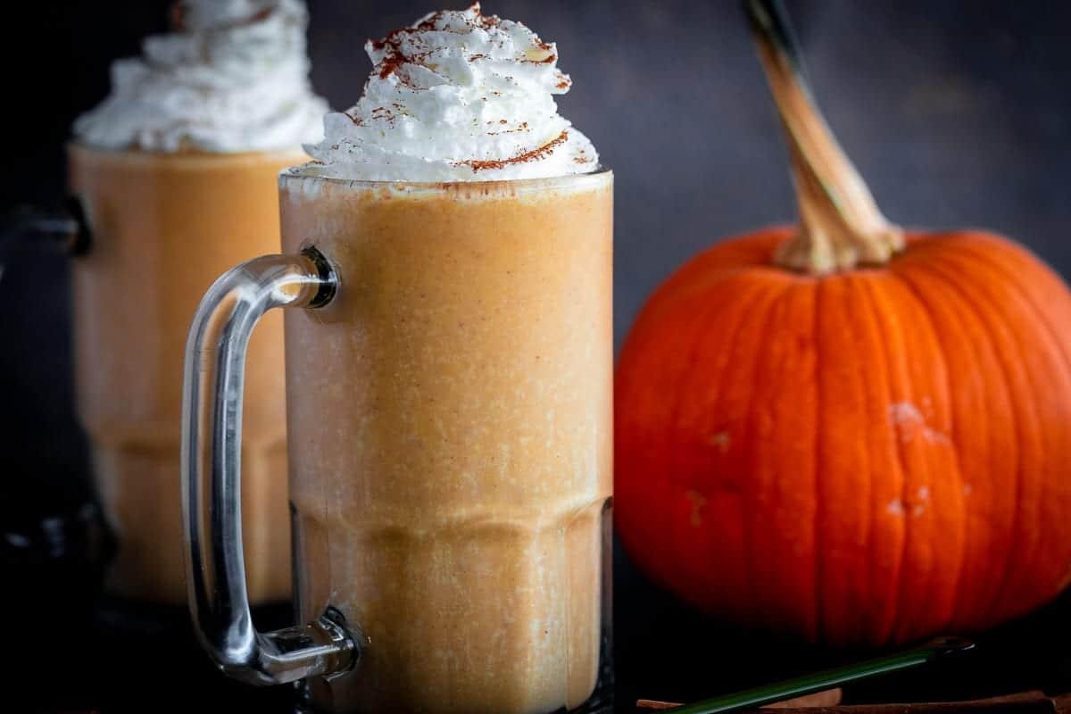 Simple Pumpkin Milkshakes in glass stein with pumpkin in the background.