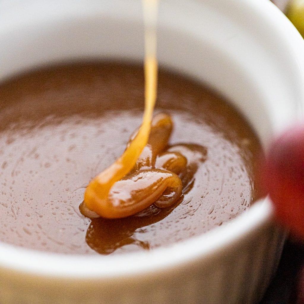 maple caramel being poured into small white ramekin