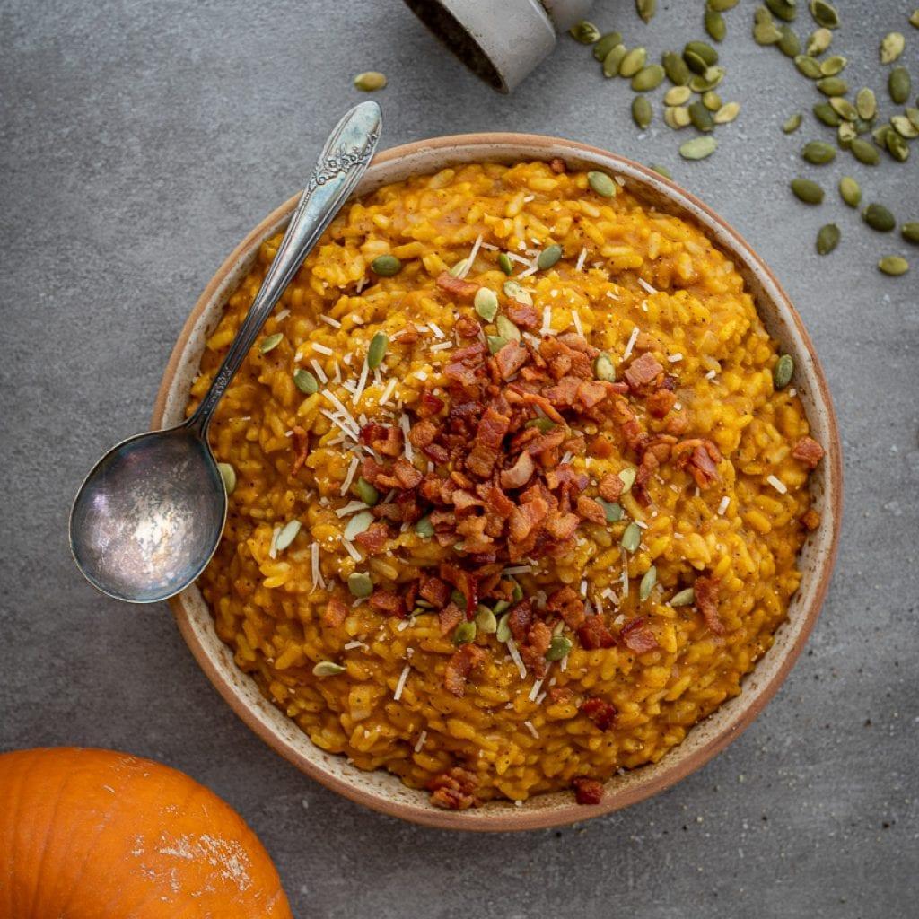 Pumpkin risotto with crispy bacon in ceramic dish