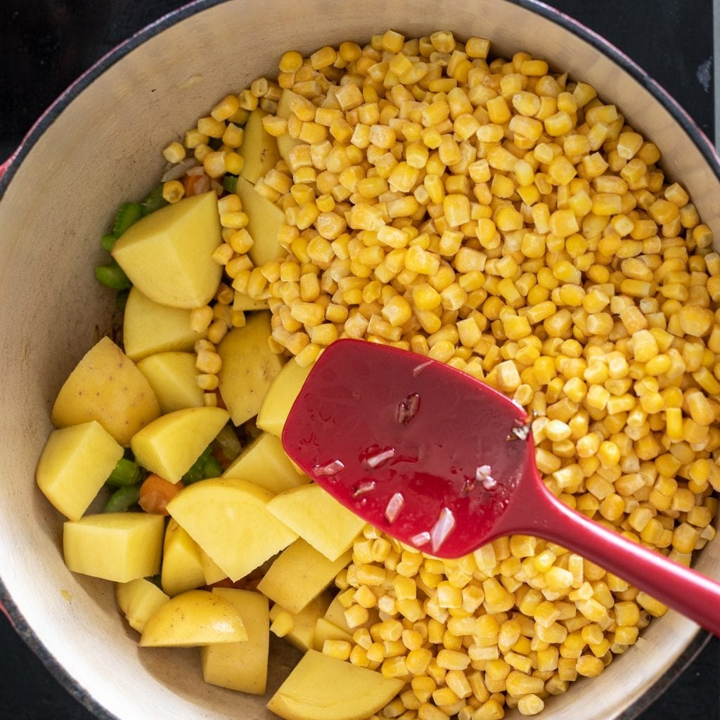 corn and potatoes in enameled dutch oven