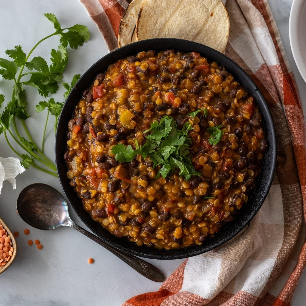 Southwestern Vegetable Soup with Lentils with tortillas and cilantro and lentils on surface