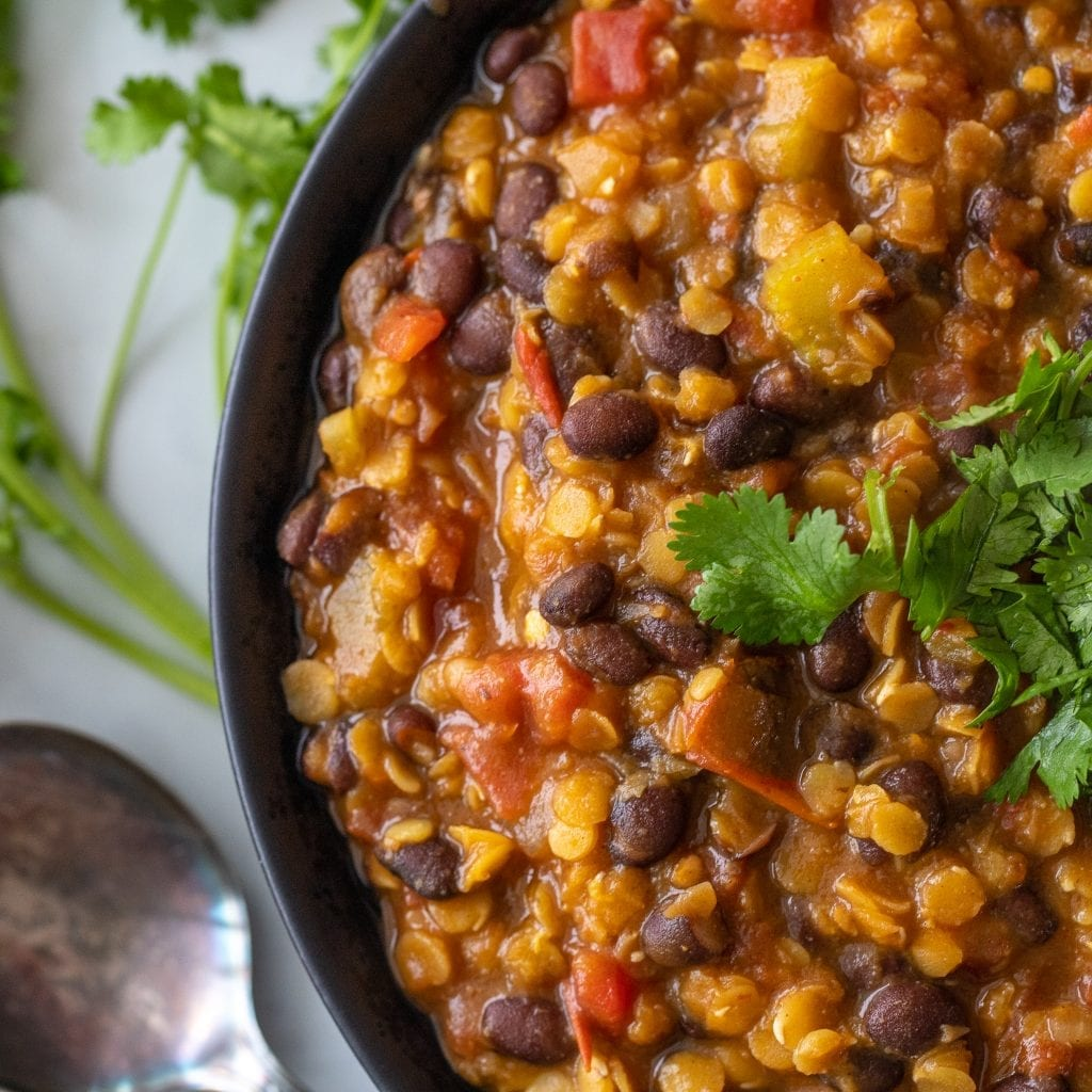 Southwestern Vegetable Soup with Lentils in black bowl on surface