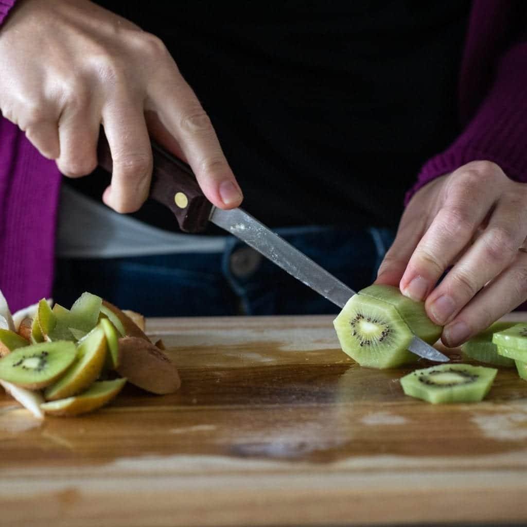 woman cutting up kiwi for fruit salad