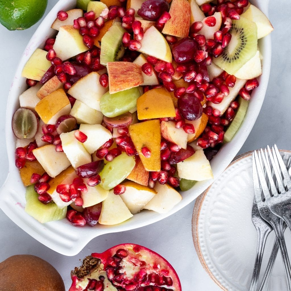 fall fruit salad with pears in a white dish with lime and dressing on the side
