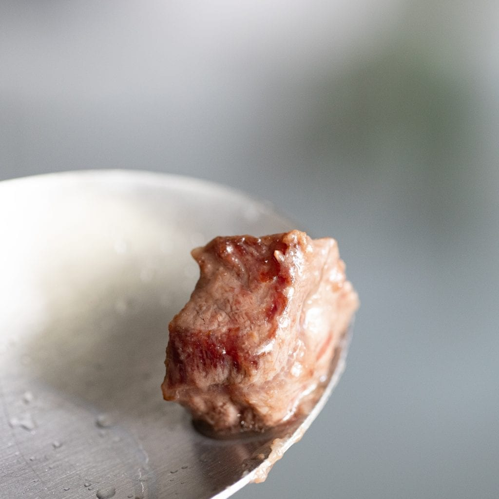 cook beef chunk for soup on large metal spoon