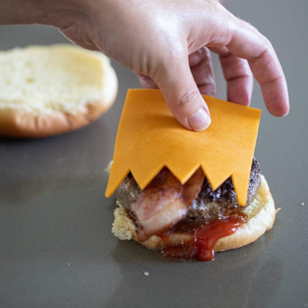 woman adding cheese teeth to monster Halloween burger