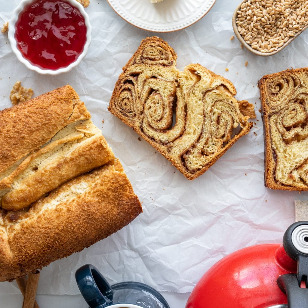 Povitica-Style Swirled Brioche sliced on parchment paper with teapot and mug