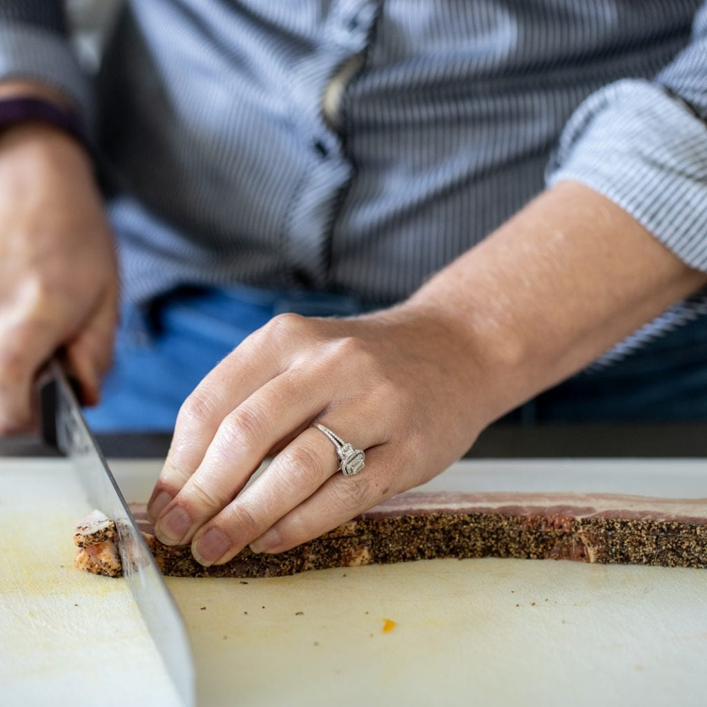 woman cutting bacon into small pieces for frying