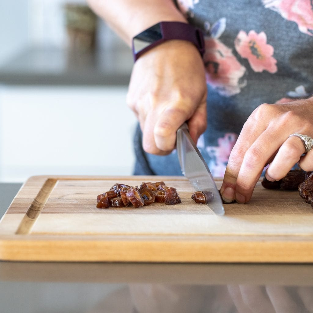 woman cutting dates on wooden cutting board