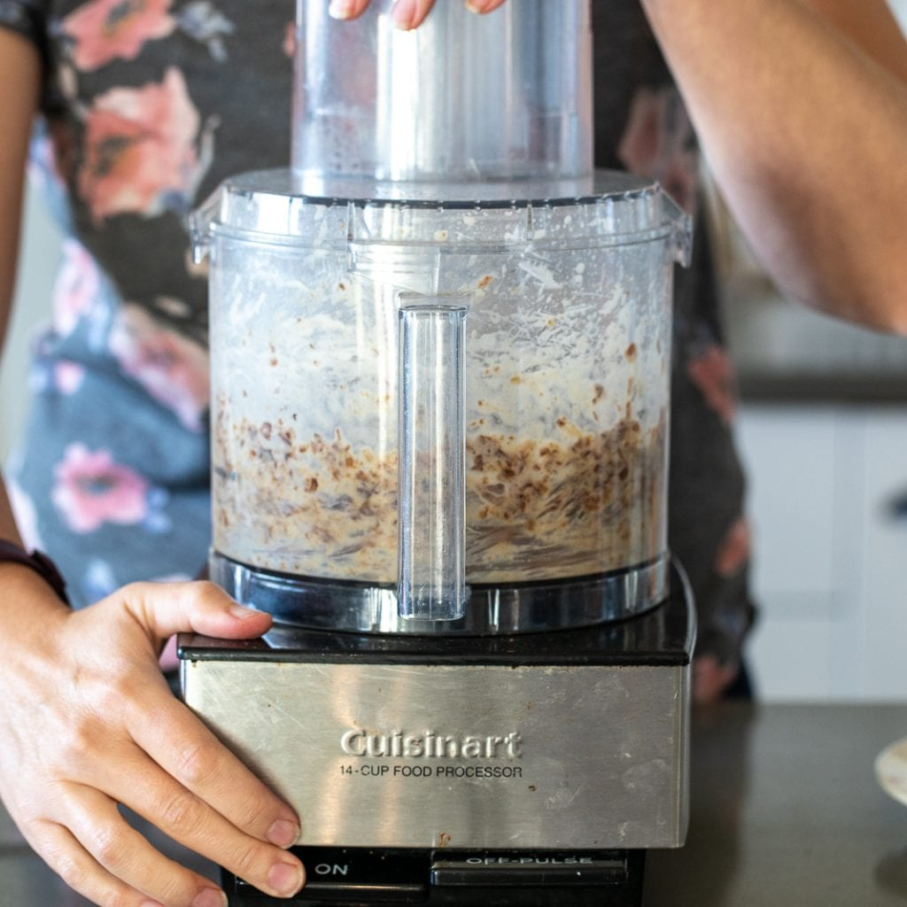 woman mixing date caramel and peanut butter in food processor