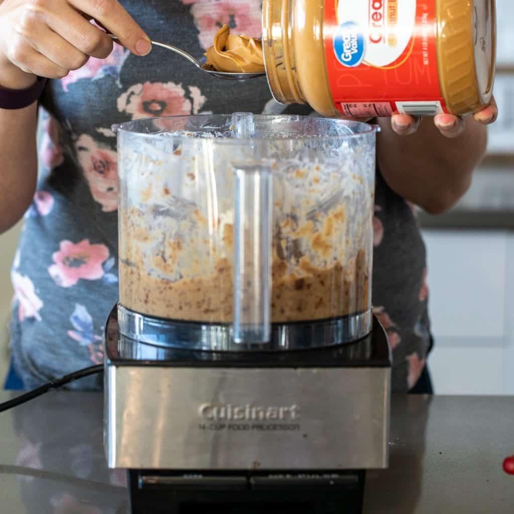 woman adding peanut butter to food processor for date caramel peanut butter dip