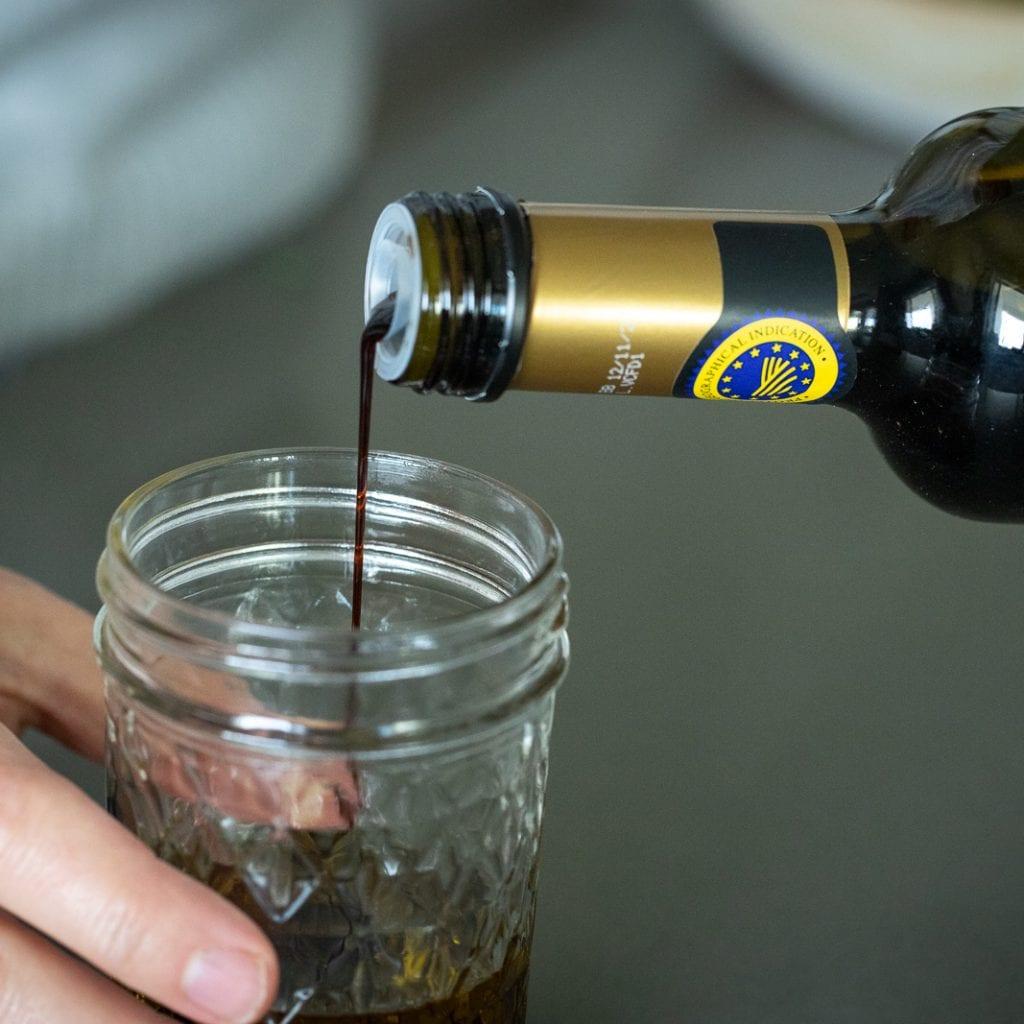 woman putting balsamic into small glass jar for a vinaigrette