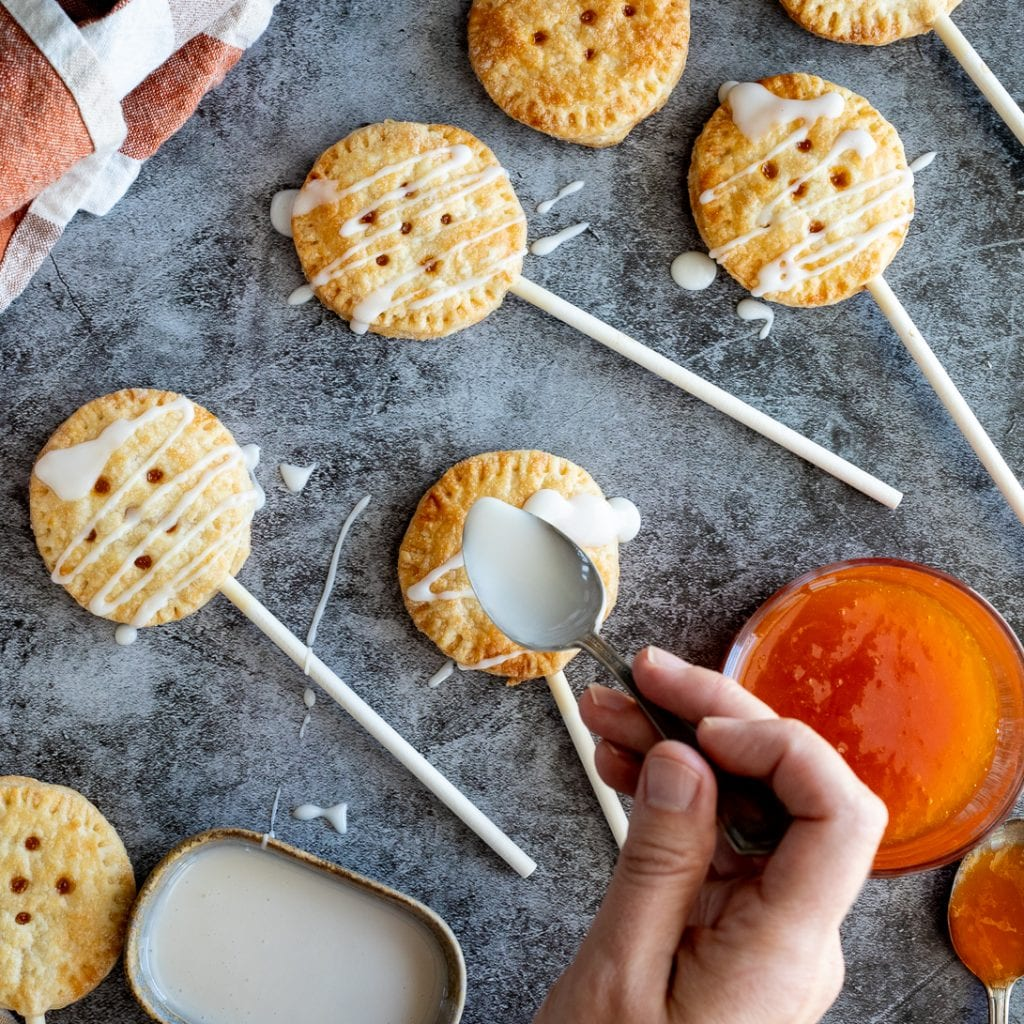 Simple Baked Pie Pops on slate surface with apricot jam drizzle with icing