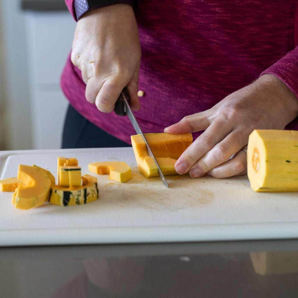 woman cutting delicata slices down for roasting with a boning knife