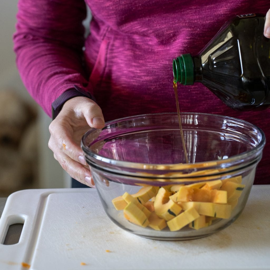 woman pouring olive oil over delicata squash for salad