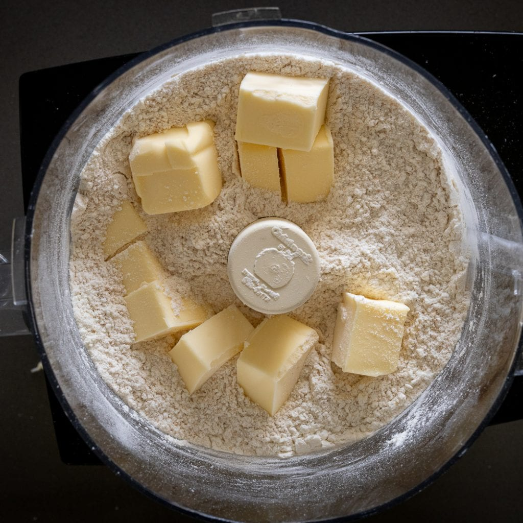 butter on top of dry ingredients in Cuisinart food processor for making pie dough