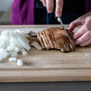 woman slicing onions and portabella mushrooms on wooden cutting board.