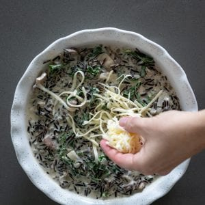 woman sprinkling gruyere cheese on a wild rice casserole bake in a ceramic pie plate