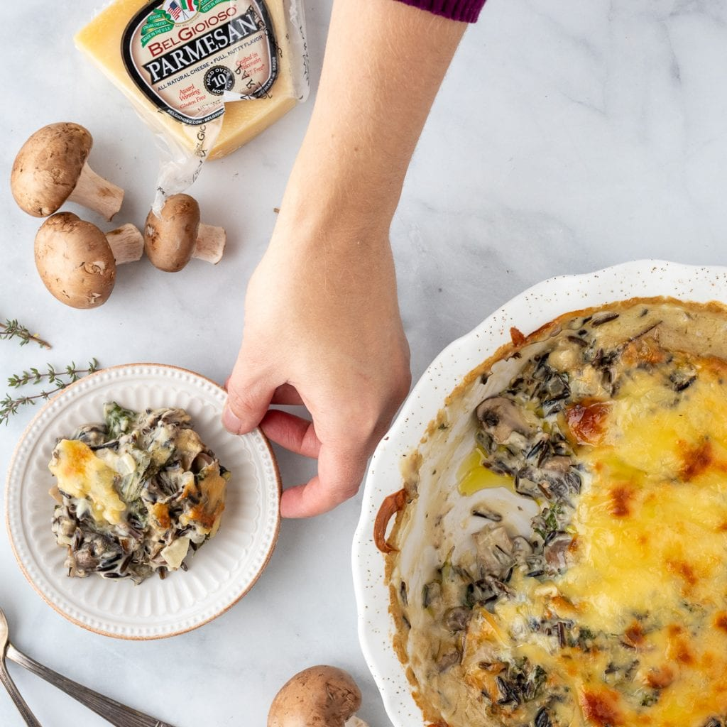 woman holding serving plate of wild rice casserole with mushrooms