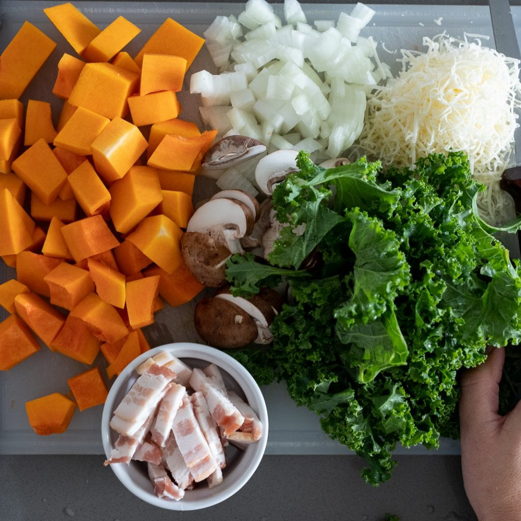 cut butternut squash, onions, kale, parmesan cheese, mushrooms, and bacon on a cutting board