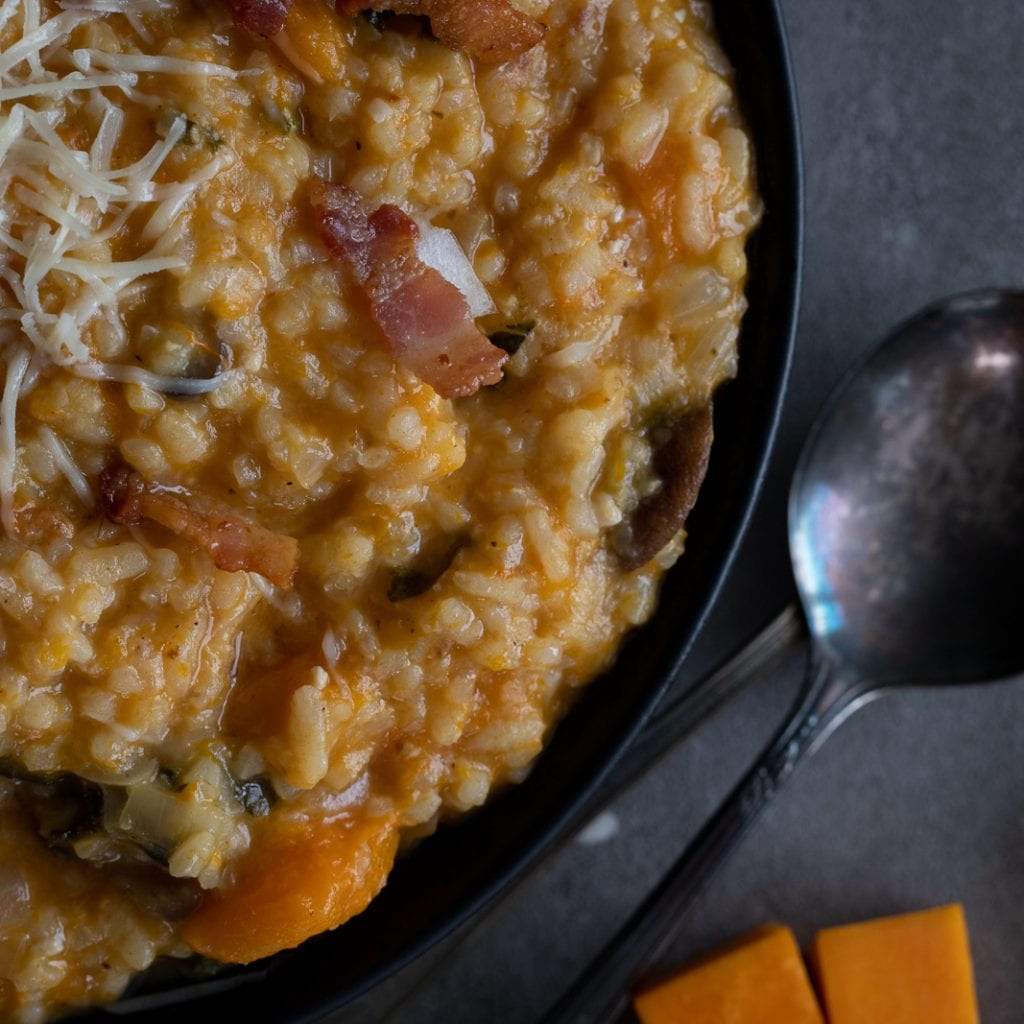 Butternut Risotto with Mushrooms and bacon in black bowl with vintage spoons at the side