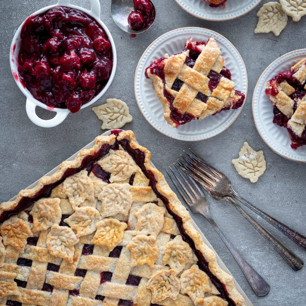 cherry slab pie on a slate  surface with slice on small plates and antique forks