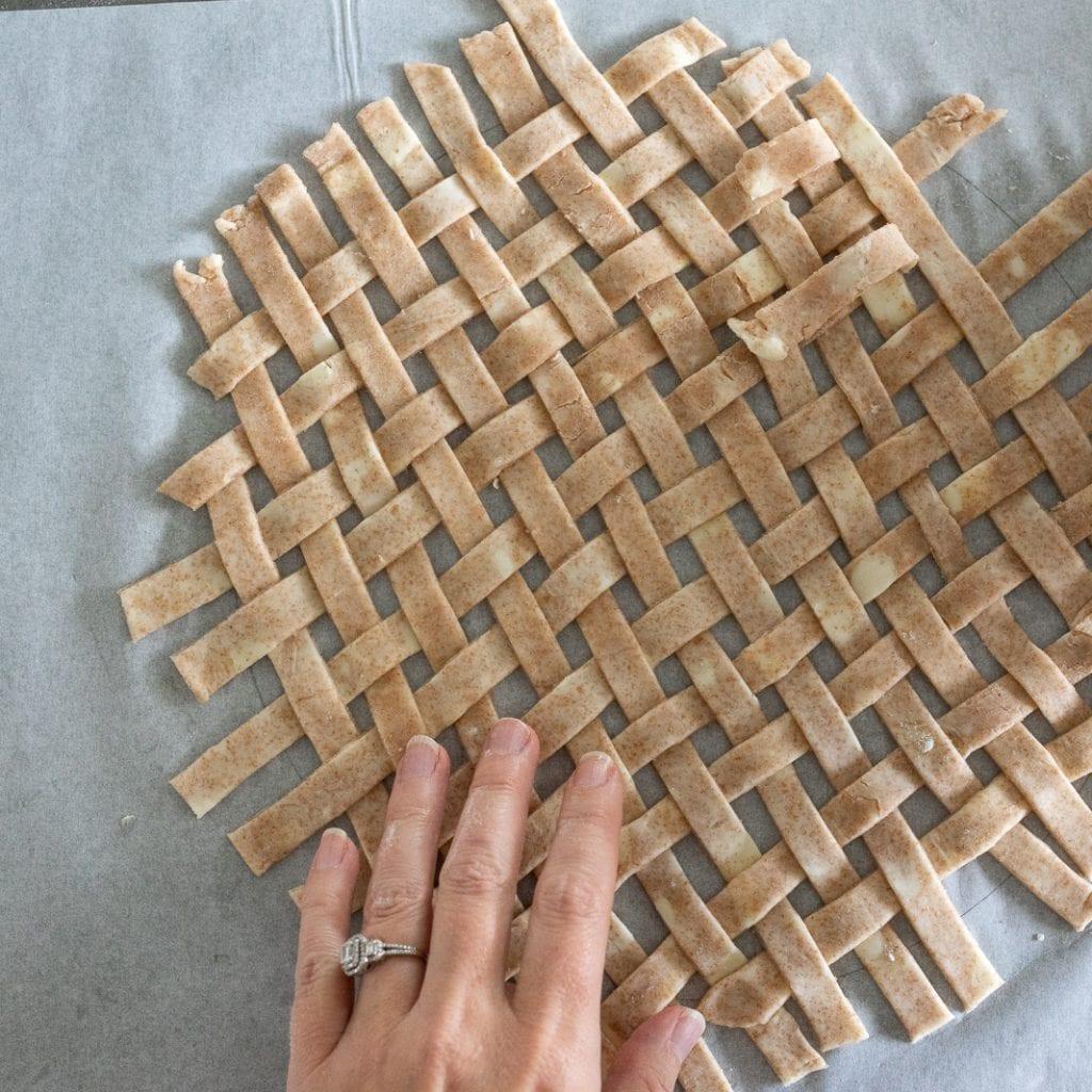 woman weaving pie dough strip to create latticework for pie topping