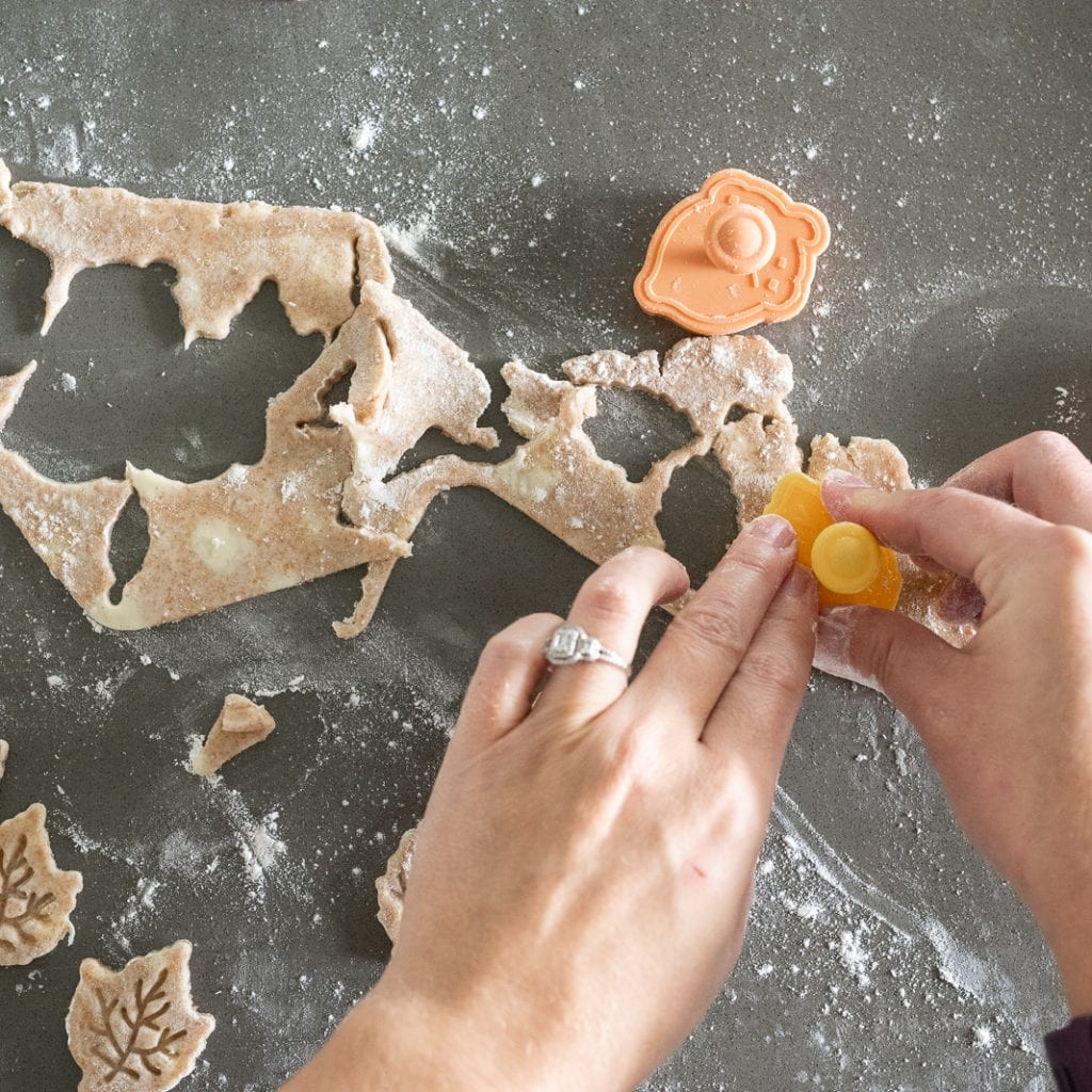 woman cutting leaves and acorns from pie dough for decoration on an apple pie