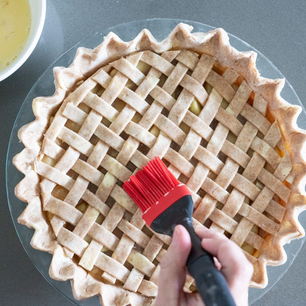 woman brushing an egg wash on an apple pie