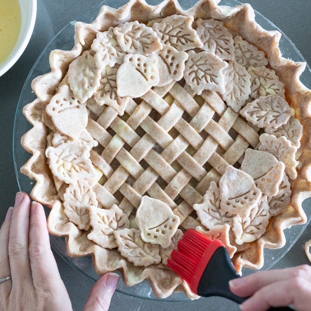 woman brushing leaf decorations on an apple pie with latticework