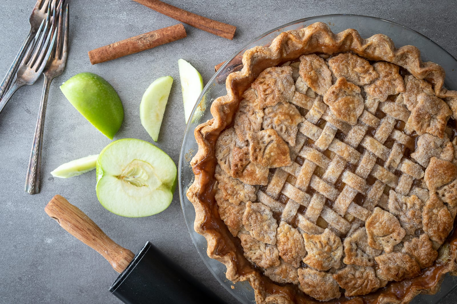 The perfect apple pie baked in glass pie plate with apples and cinnamon sticks on the side