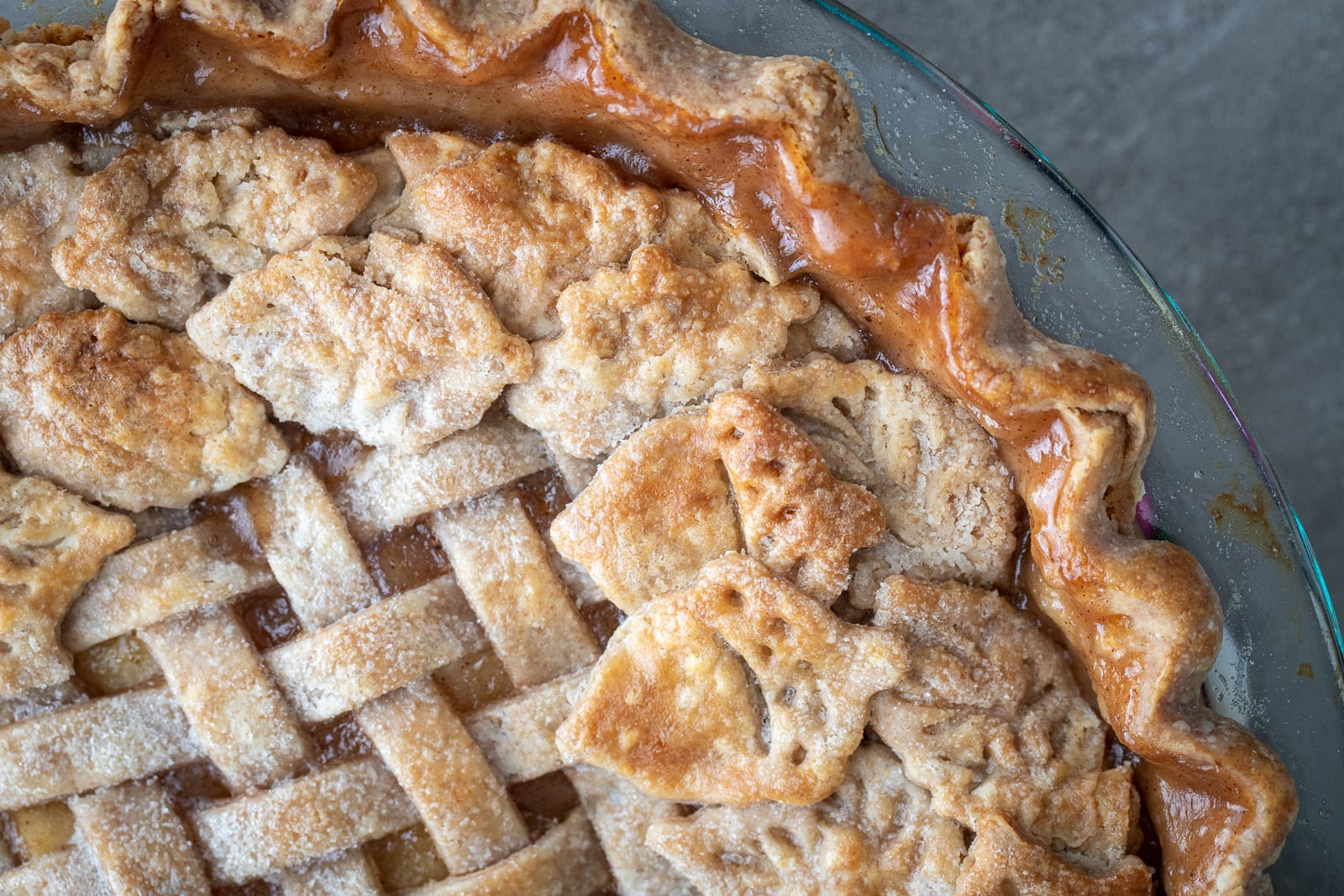 The Perfect Apple Pie baked in a glass pie plate with leaves and acorn pie decorations