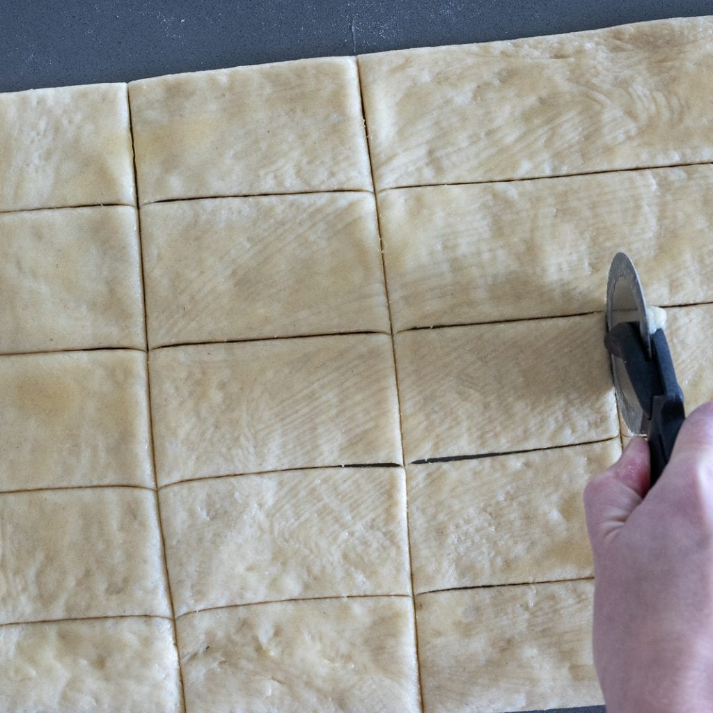 woman cutting parker house rolls into rectangles for holiday meal