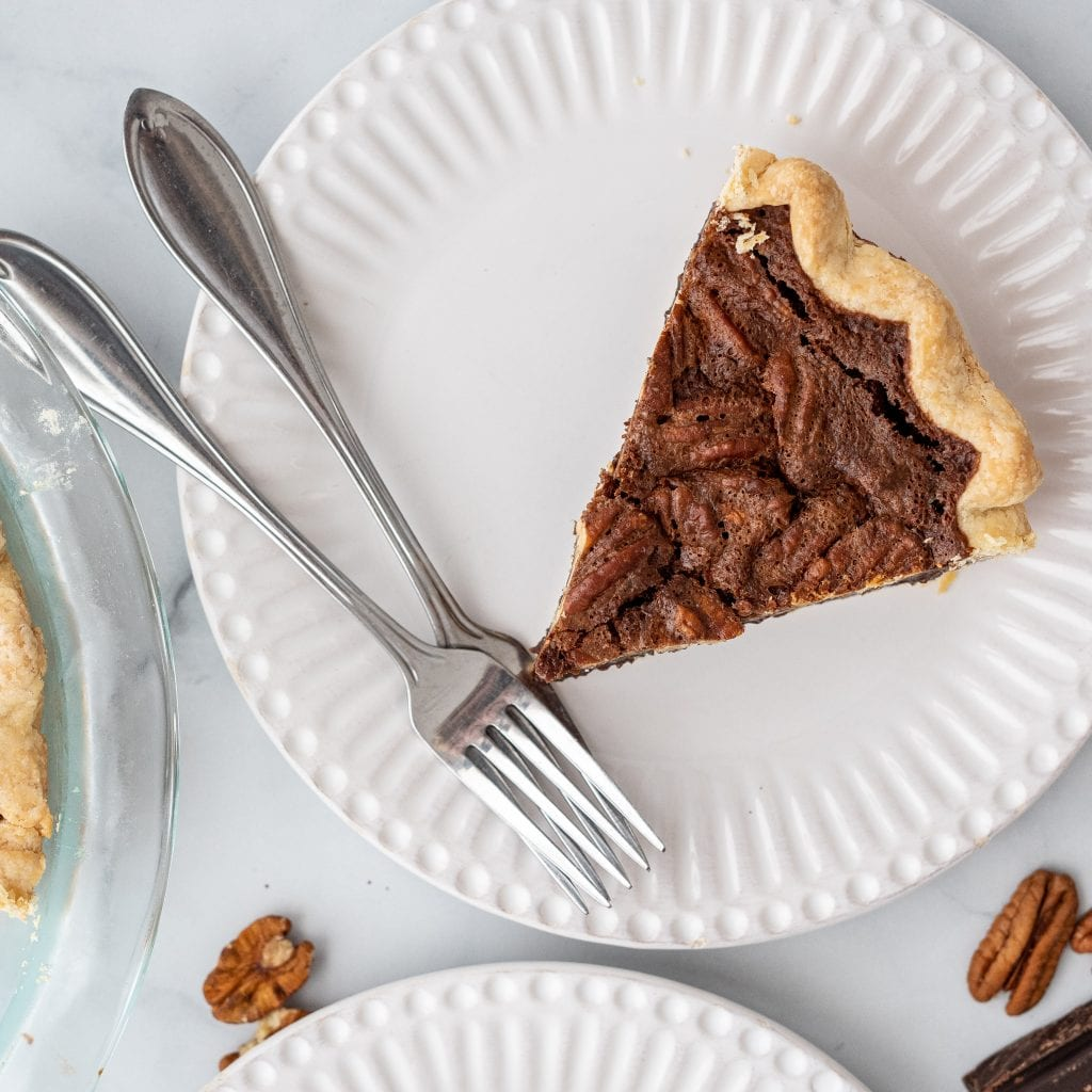 chocolate pecan pie on small white plate with 2 forks