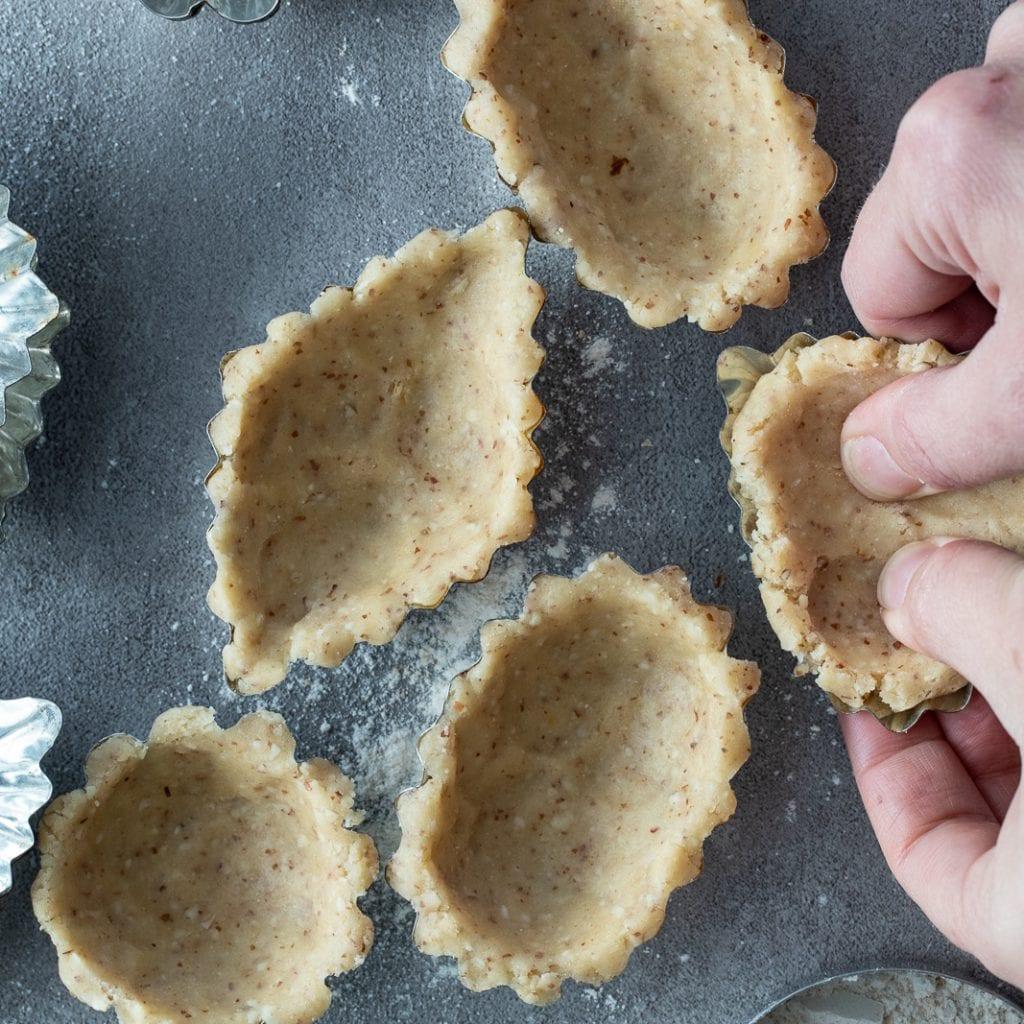 woman pressing mandelmusslor dough into tartlet pans for baking.