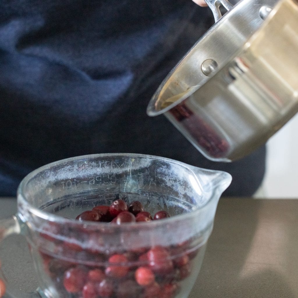woman pouring simple syrup over cranberries to make sugared cranberries